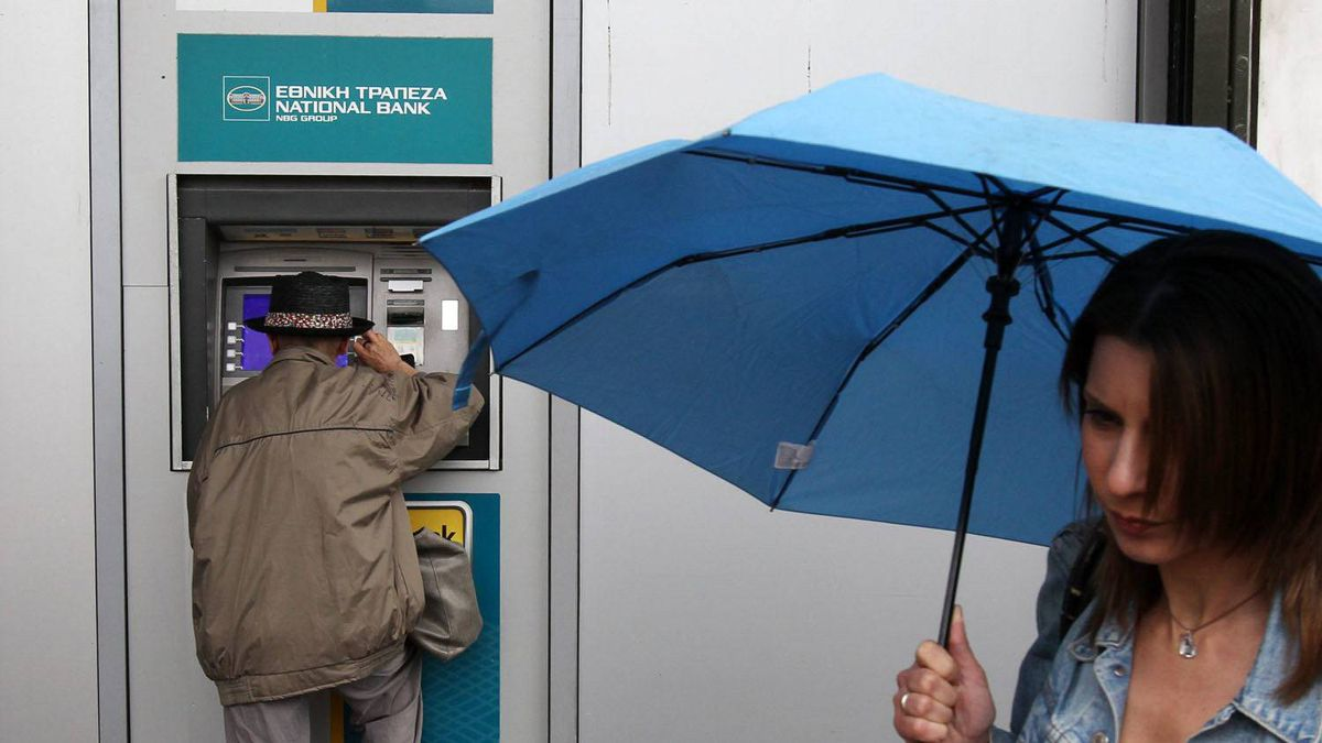 A woman with an umbrella walks past a man using an ATM of the National Bank of Greece in Athens, Friday, May 18, 2012.