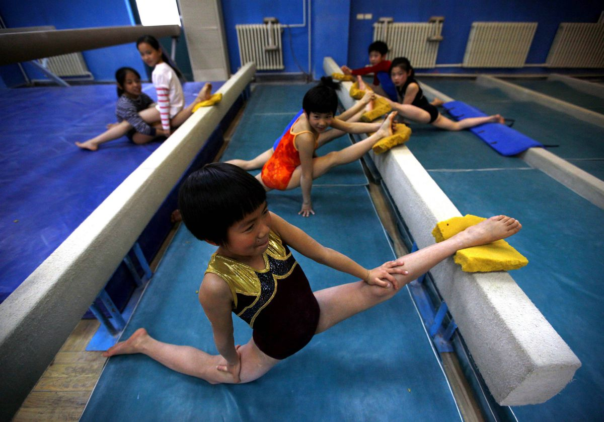A young gymnast stretches with her classmates. About half the students pay their own way with the other half, called 'professional reserves,' having all their training, academic and accommodation expenses covered by the state.