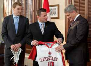Prime Minister Stephen Harper accepts an official 2010 Team Canada lacrosse jersey from players Brodie Merrill and Geoff Snider at his Langevin Block office on Monday, November 23, 2009.