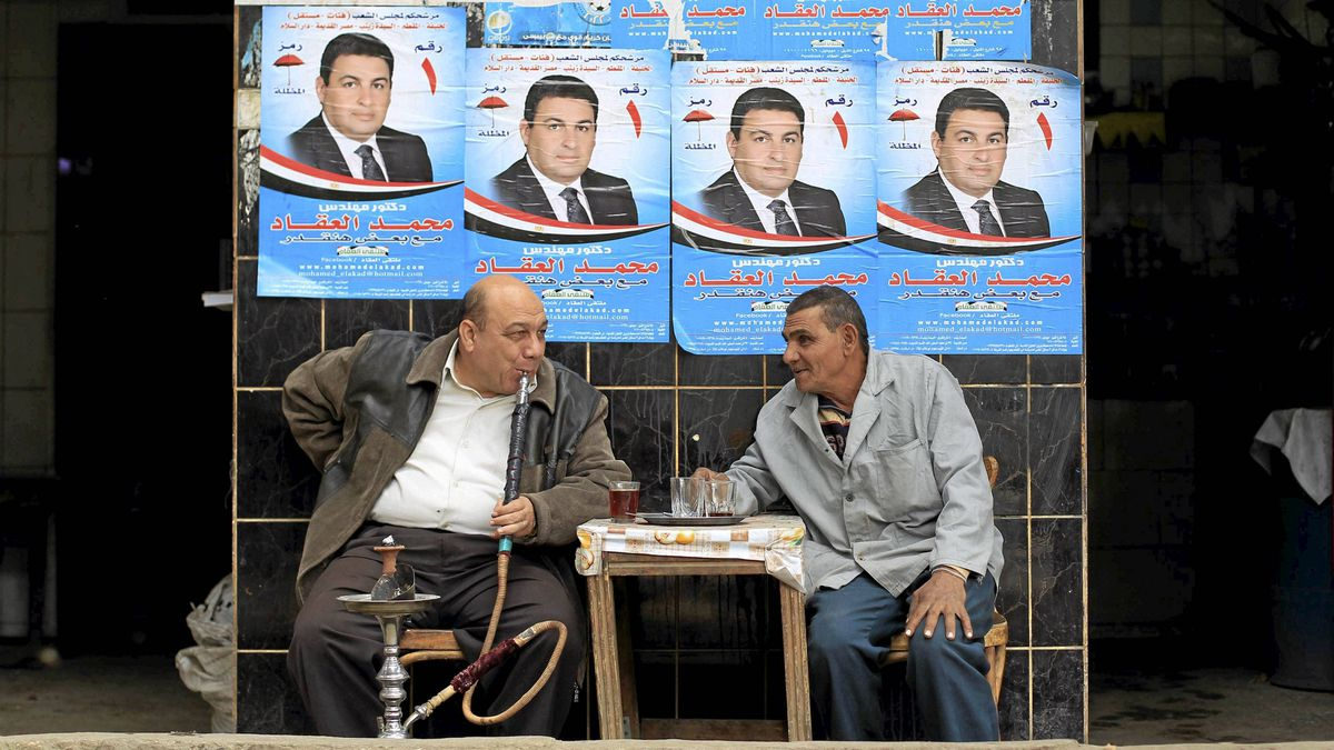 An Egyptian smokes water pipe in front of election campaign banners at a cafe in Cairo Nov. 27, 2011.