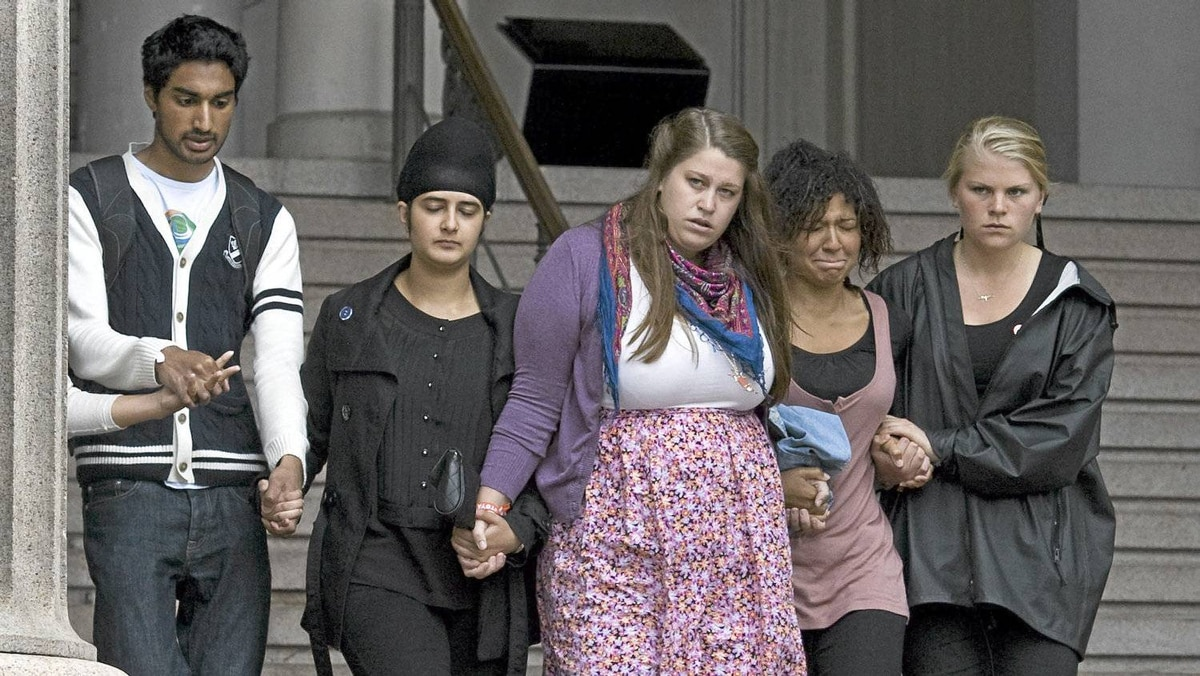 Family members and survivors embrace as they queue to sign the book of condolences in Oslo on July 25, 2011. Prableen Kaur, 23, (second left) is deputy leader of Norway's Labour Party youth wing. She was caught in the shooting, escaped by playing dead and eventually swam to safety.