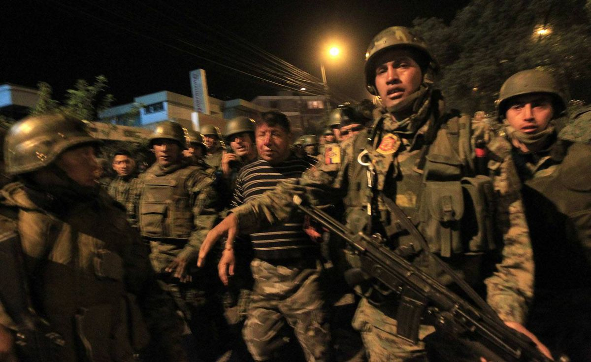 Soldiers escort a wounded companion during clashes with striking police outside a hospital where Ecuador's President Rafael Correa was holed up inside, in Quito. Guillermo Granja/Reuters
