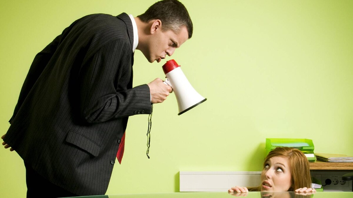A boss yells into a megaphone while a worker cowers at a desk.