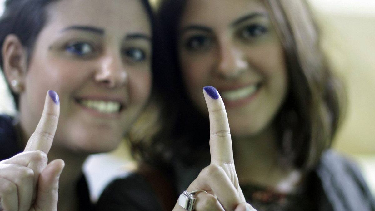 Young women show their inked fingers after voting in an election that Egyptians hope will usher in a democratic age after decades of dictatorship.