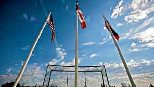 Flags blow in the wind at the baseball diamond in the town of Emerson, Man., on Oct. 10, 2010.