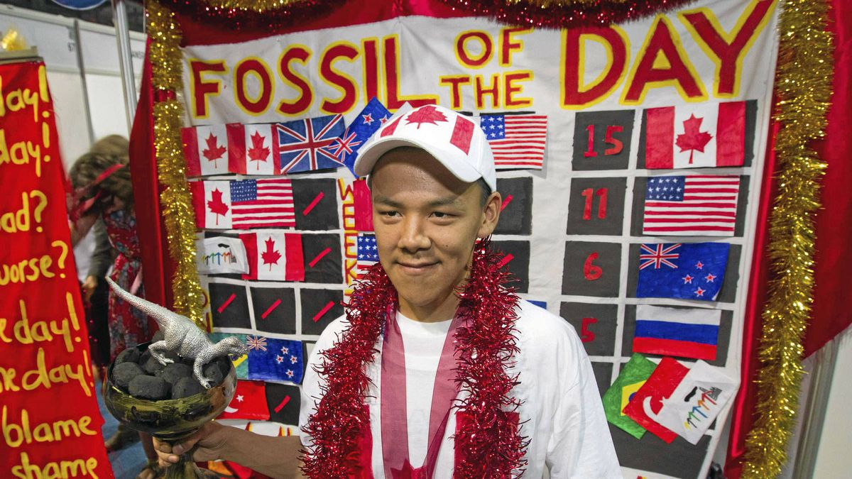The Colossal Fossil mock award is presented to Jordan Konek, an Inuit from the town of Arviat in Nunavut, in Durban Dec. 9, 2011. Canada has received the Fossil of the Year award for five years running, which mark what activists call the country's poor performance in global climate progress.