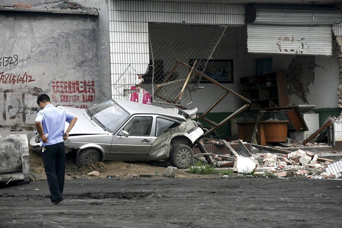 In this photo taken Sunday, Aug. 1, 2010, a policeman walks near a smashed car and shop at Yuanshi county, in north China's Hebei province. A drunken shovel loader driver went on a rampage in northern China, smashing into shops and vehicles and killing 11 people, a government spokesman said Monday.