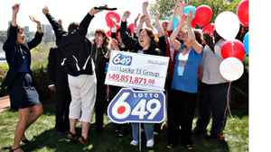 13 workers from ATB Financial in Edmonton celebrate on Friday May 22 after they won $49,851,871 in a Lotto 649 jackpot.