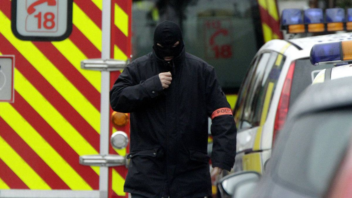 A masked French special intervention police (RAID) member arrives on the scene during a raid on a house to arrest suspects, involved in the killings of three children and a rabbi on Monday at a Jewish school, in Toulouse March 21, 2012.
