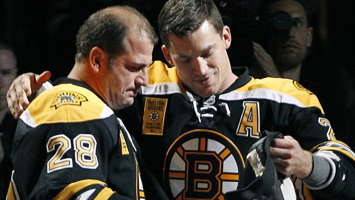 Retired Boston Bruins' Mark Recchi (28) receives the coveted team jacket from Andrew Ference prior to their NHL hockey season-opening game against the Philadelphia Flyers in Boston Thursday, Oct. 6, 2011. (AP Photo/Elise Amendola)
