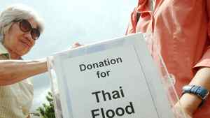A donor puts money into a donation box for the Thai flood victims, at a Buddhist temple in Kuala Lumpur on Feb. 27, 2011.