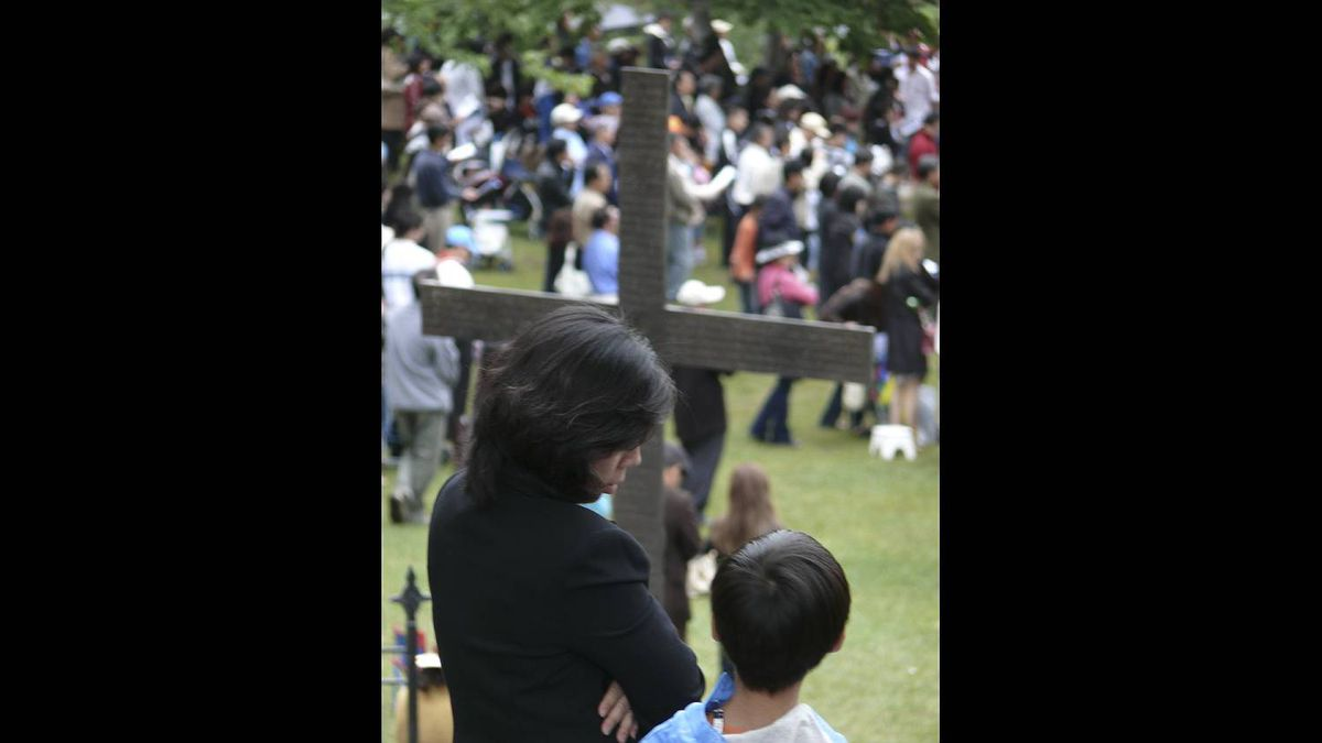 Jim Shaw photo: Mother and Son wait under the cross for Mass to Begin