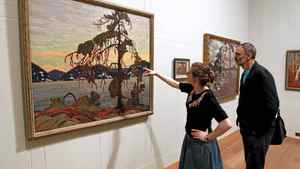 """Exhibition officer Amy Concannon (L) and designer Eric Pearson view Canadian artist Tom Thomson's 1917 oil painting """"The Jack Pine"""" at the Dulwich Picture Gallery in London on Oct. 14, 2011. The gallery is hosting """"Painting Canada: Tom Thomson and the Group of Seven"""" from Oct. 19, 2011 to Jan. 8, 2012."""
