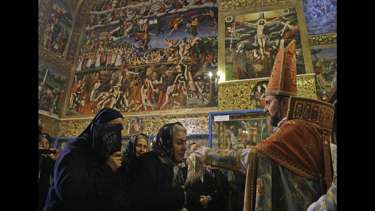 An Iranian Christian kisses the Cross held by archbishop Babken Charian, during New Year Mass at the Vank church in the central city of Isfahan, 390 km south of the capital Tehran, Iran, Sunday, Jan. 1, 2012.