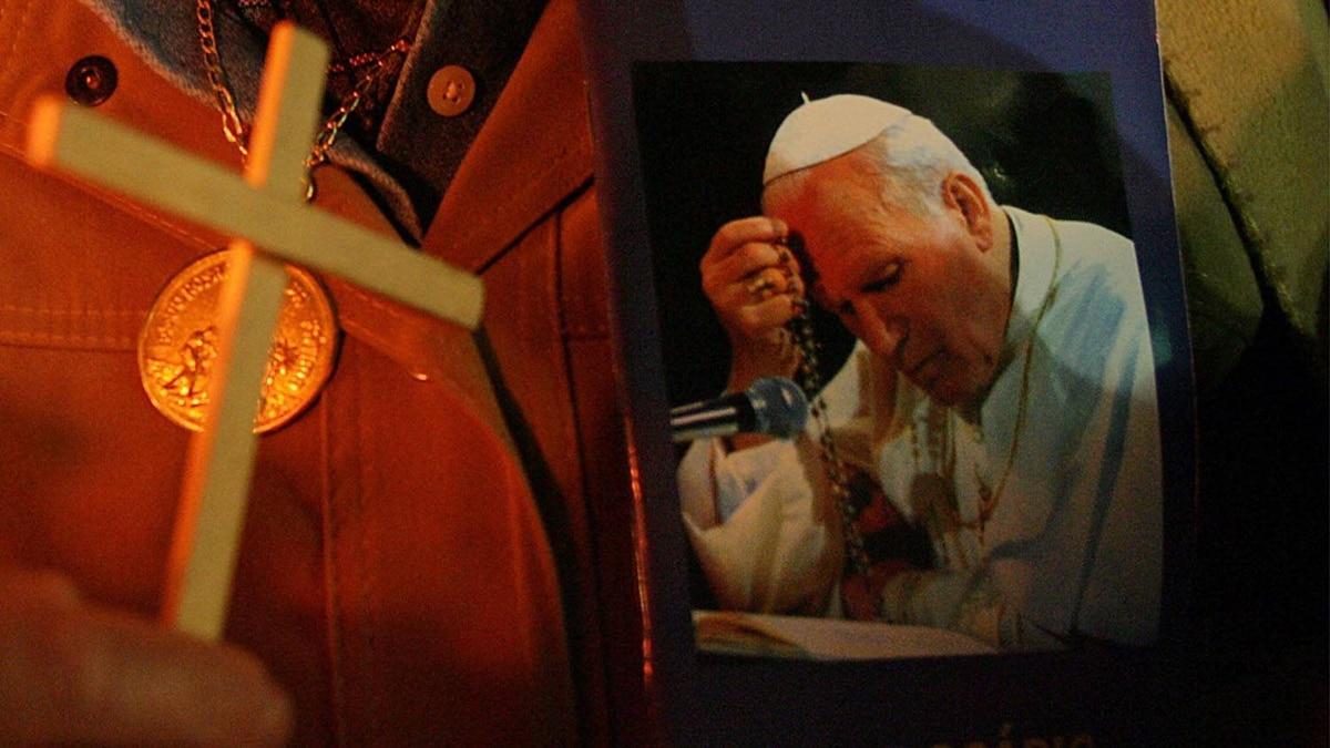 A pilgrim holds a portrait of late Pope John Paul II. Reuters
