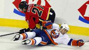 New York Islanders' Tim Wallace, right, crashes to the ice with Calgary Flames' Derek Smith during second period pre-season NHL hockey action in Calgary, Alta., Tuesday, Sept. 27, 2011.