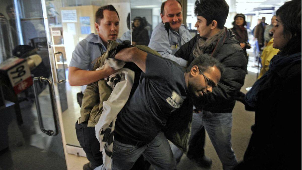 City hall security scuffle with protesters as he tries to take him to an office after the protester unfurled a banner during the traditional mayor's levee at Toronto city hall on Jan. 2, 2012.