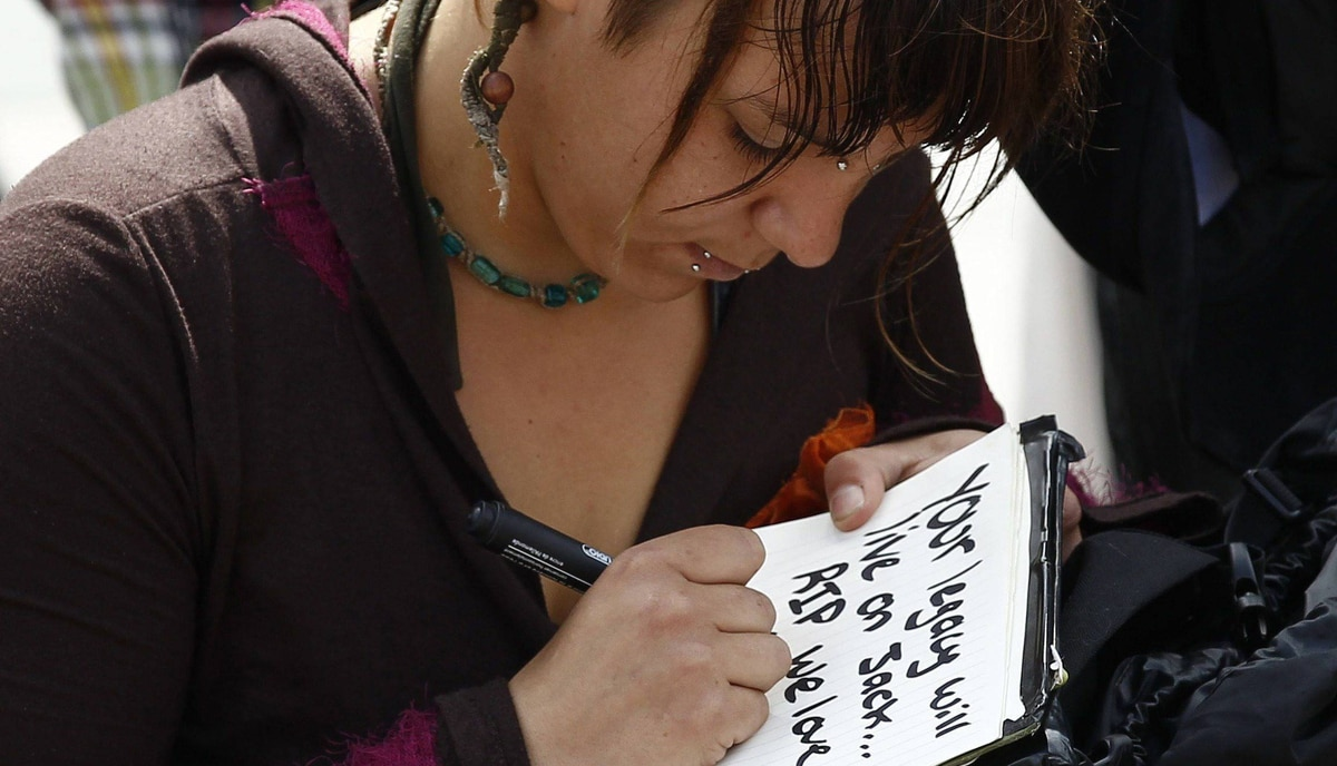 A woman writes a note while paying tribute to Jack Layton on Parliament Hill in Ottawa.