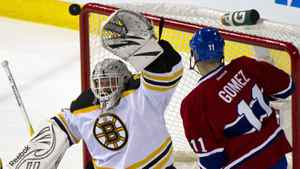 Boston Bruins goalie Tim Thomas reaches up to glove the puck as Montreal Canadiens' Scott Gomez looks for a rebound during second period NHL hockey action Wednesday, February 15, 2012 in Montreal.
