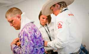 Sports therapist Krista Burton looks over bareback rider Heath Ford in preparation for day six competition in the Calgary Stampede.