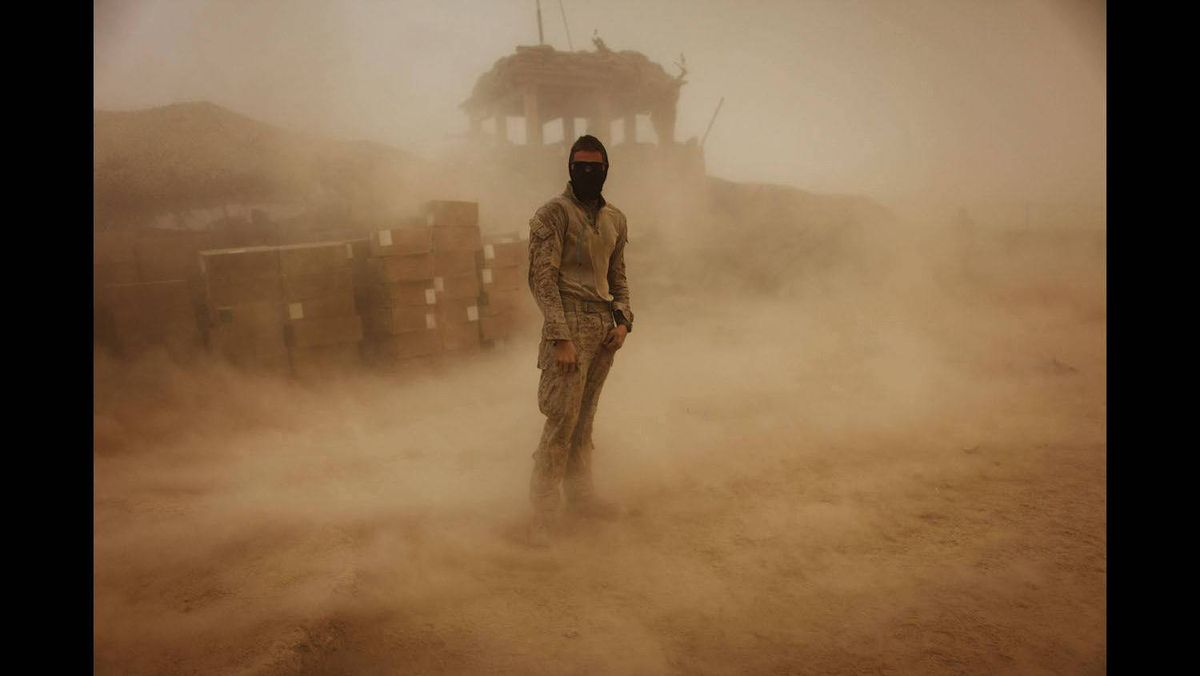 Private First Class Brandon Voris, 19, of Lebanon, Ohio, from the First Battalion Eighth Marines Alpha Company, stands in the middle of his camp as a sandstorm hits his remote outpost near Kunjak in southern Afghanistan's Helmand province, October 28, 2010.
