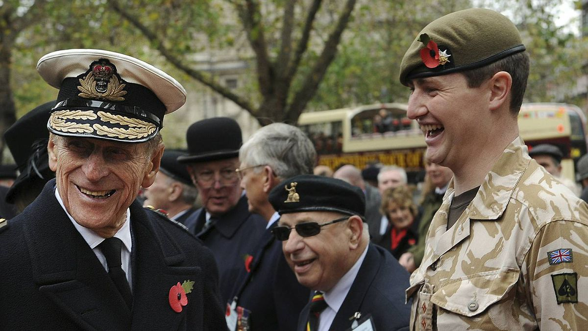 Britain's Prince Philip (L), reacts as he meets with representatives of British military regiments, during a service in which he opened the Field of Remembrance at Westminster Abbey, in central London on November 11, 2010. Prince Philip went on to lay a wreath at the grave of the Unknown Warrior, as part of this year's Armistice Day memorial services.