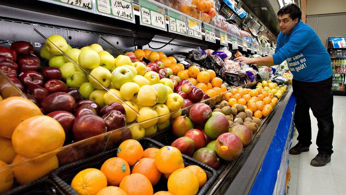 Grocery store owner Gilles Robin works on his fruits vegetable display on Nov. 28 2006 in Breakeyville, Que. Food inflation is likely to cool in 2012, analysts say.