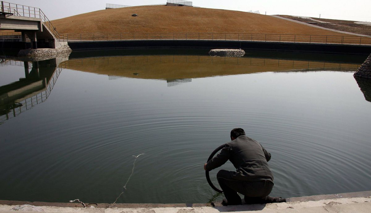 A security guard tries to find the puncture in the inner-tube of his bicycle tyre by immersing it in the deserted and unmaintained former course for the kayaking competition of the 2008 Beijing Olympic Games, located on the outskirts of Beijing March 27, 2012.