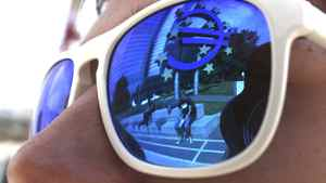 A euro sign is mirrored in sunglasses of a person standing in front of the European Central Bank headquarters in Frankfurt.