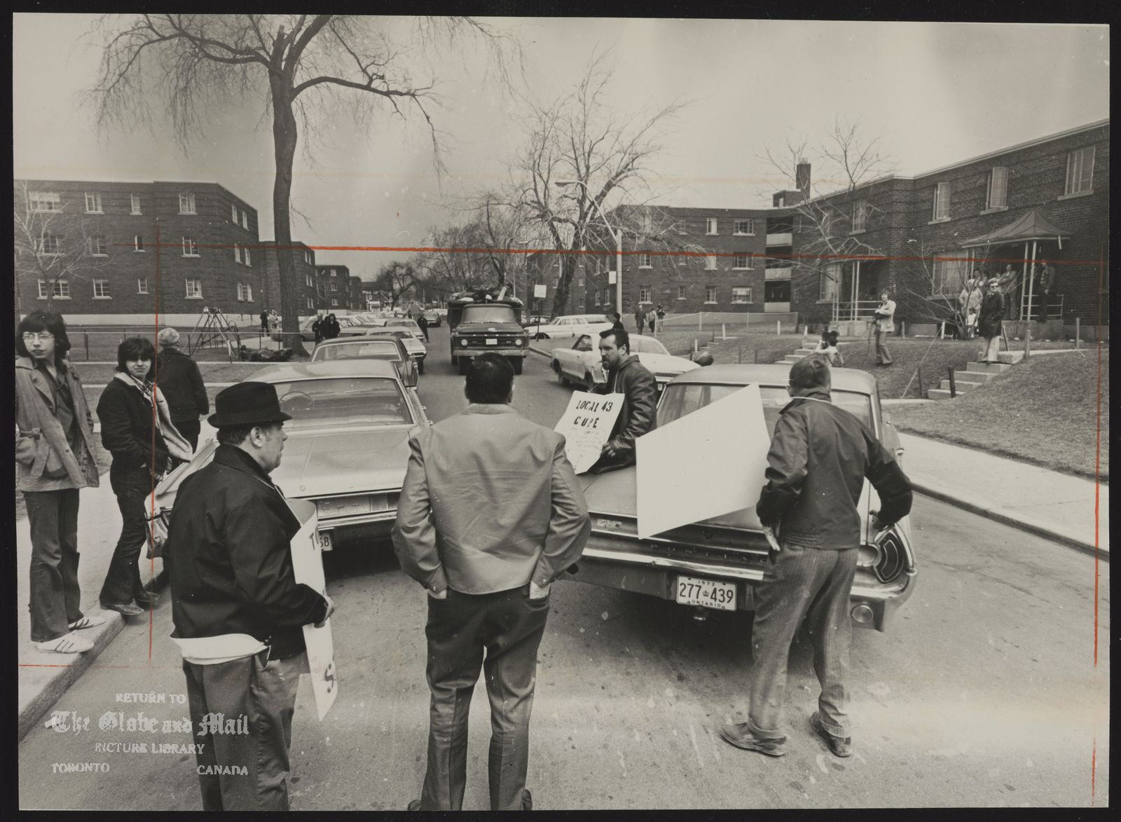 The notes transcribed from the back of this photograph are as follows: (striking workers blocked road with a car to garbage truck from Ontario Housing servicing Regent park)