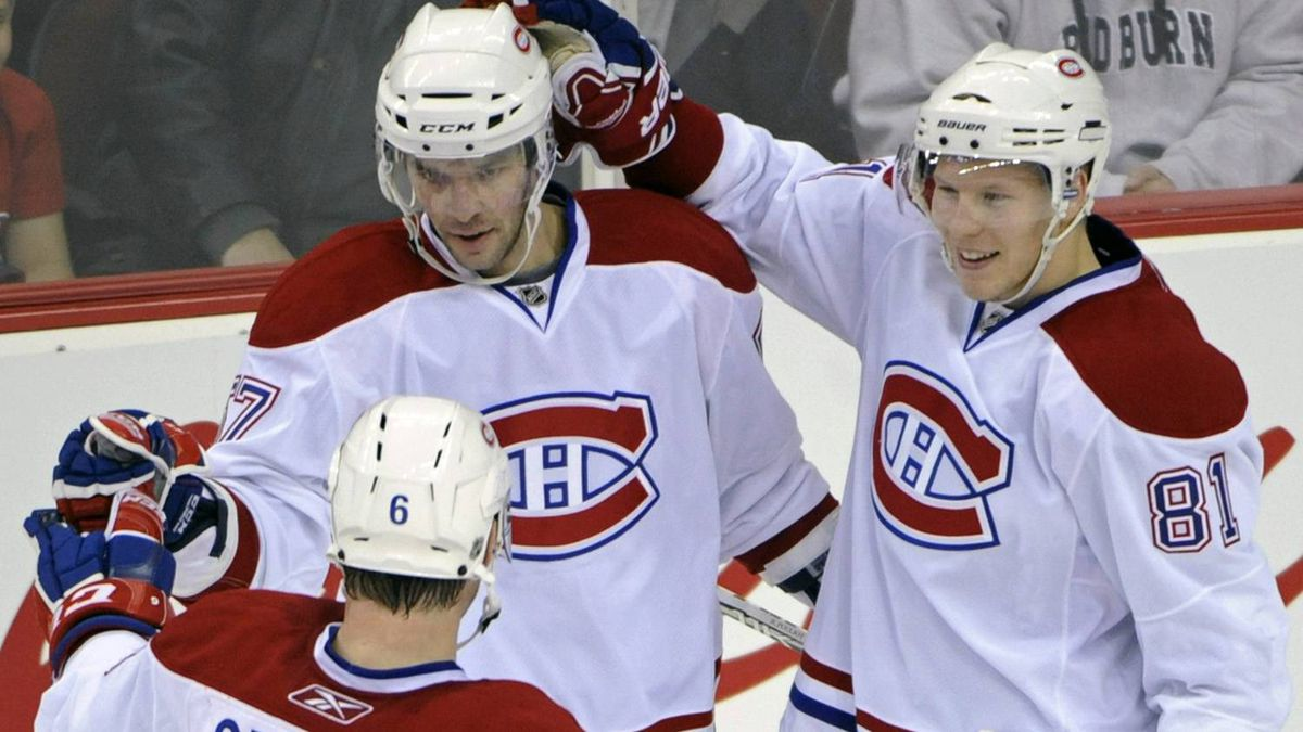 Montreal Canadiens' Benoit Pouliot celebrates with Jaroslav Spacek (6) and Lars Eller, right, after Pouliot scored during the second period of an NHL hockey game against the New Jersey Devils, Thursday, Dec. 2, 2010, in Newark, N.J. The Canadiens won 5-1.