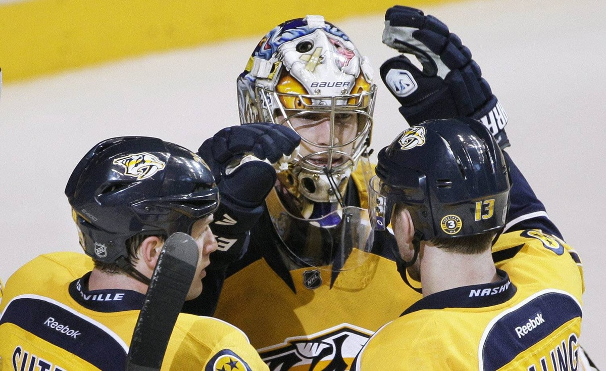 Nashville Predators goalie Pekka Rinne, center, of Finland, is congratulated by Ryan Suter (20) and Nick Spaling (13) after the Predators defeated the Detroit Red Wings 3-2 in Game 1 of a first-round NHL hockey playoff series on Wednesday, April 11, 2012, in Nashville, Tenn.