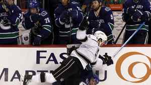 Los Angeles Kings center Mike Richards (10) hits Vancouver Canucks right wing Alex Burrows (14) in front of the Canucks bench in the 3rd period during Game 1 their NHL Western Conference quarter-final hockey playoffs in Vancouver, British Columbia April 11, 2012. The Kings won 4-2.