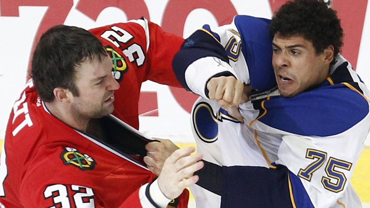 St. Louis Blues' Ryan Reaves (R) and Chicago Blackhawks' John Scott fight during the first period of their NHL hockey game in Chicago, February 19, 2012. The Blackhawks won 3-1. REUTERS/Jim Young