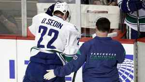 Vancouver Canucks left wing Daniel Sedin (22) his helped off the ice in the first period of his NHL hockey game against the Chicago Blackhawks in Chicago, March 21, 2012.