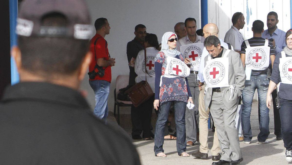 Members of the International Red Cross wait at the Rafah crossing with Egypt in the southern Gaza Strip as the Israeli-Palestinian prisoner swap deal gets under way.