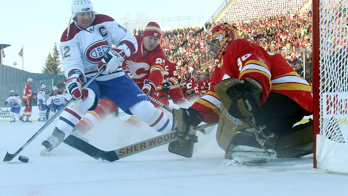 Mike Vernon #30 of the Calgary Flames Alumni makes the stop on Mike Keane #12 of the Montreal Canadiens Alumni during the Alumni game held as part of the 2011 NHL Heritage Classic festivities at McMahon Stadium on February 19, 2011 in Calgary, Alberta, Canada. (Photo by Andre Ringuette/Getty Images)