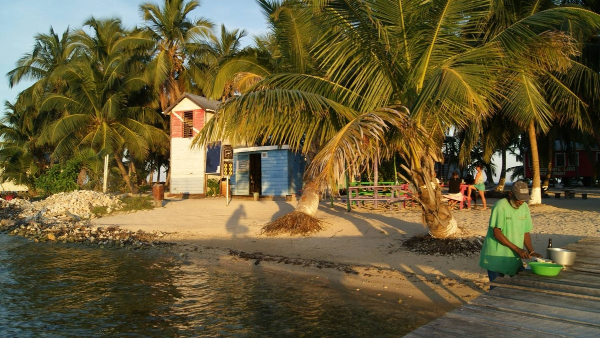 Local resident George prepares potatoes for dinner while the sun sets on Tobacco Caye