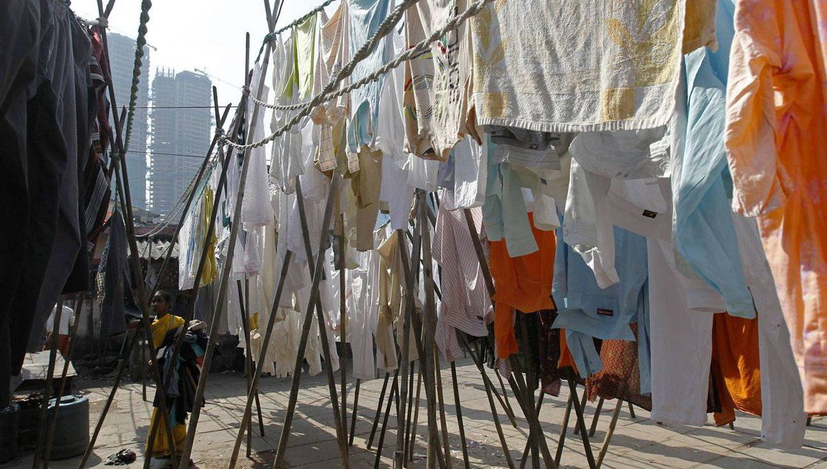 A laundrywoman retrieves clothes hung out to dry at the Dhobi Ghat open air laundry in Mumbai.