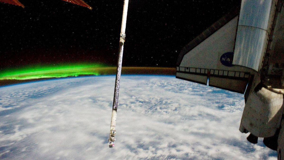 IN SPACE - JULY 16:The Southern Lights or Aurora Australis (L), the port side wing of NASA space shuttle Atlantis (R) and its Orbital Boom Sensor System robot arm extension (C) can be seen from the International Space Station July 16, 2011 in space.