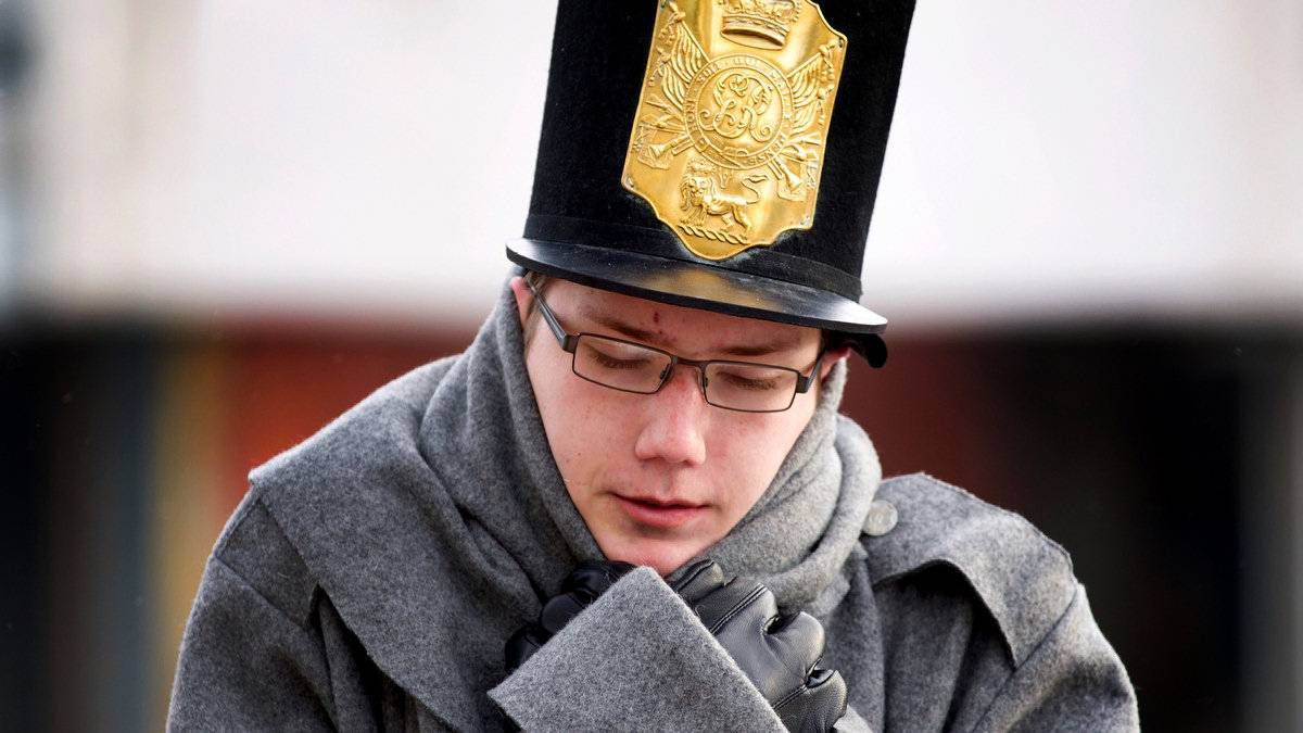 Marcus Kuehner, 15, dressed as soldier with the 41st Regiment Foot, pulls his overcoat closer against the bitter wind and cold.