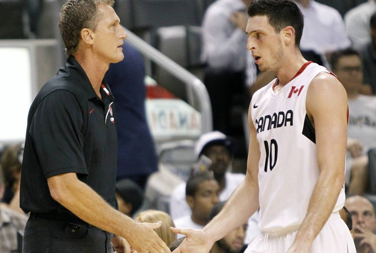 Team Canada's head coach Leo Rautins (L) shakes hands with his son and player Andy Rautins during a break in play against Team France in the first half of their exhibition FIBA basketball game in Toronto August 12, 2010. The FIBA World Championship will take place in Turkey August 28 to September 12. REUTERS/Mark Blinch