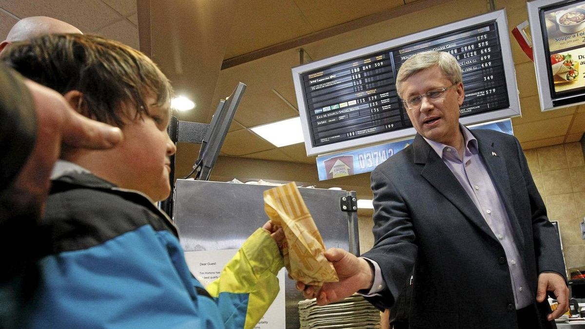 Conservative leader and Canada's Prime Minister Stephen Harper works behind the counter during a campaign stop at a Tim Hortons in Dieppe, New Brunswick April 1, 2011. Canadians will head to the polls in a federal election May 2.