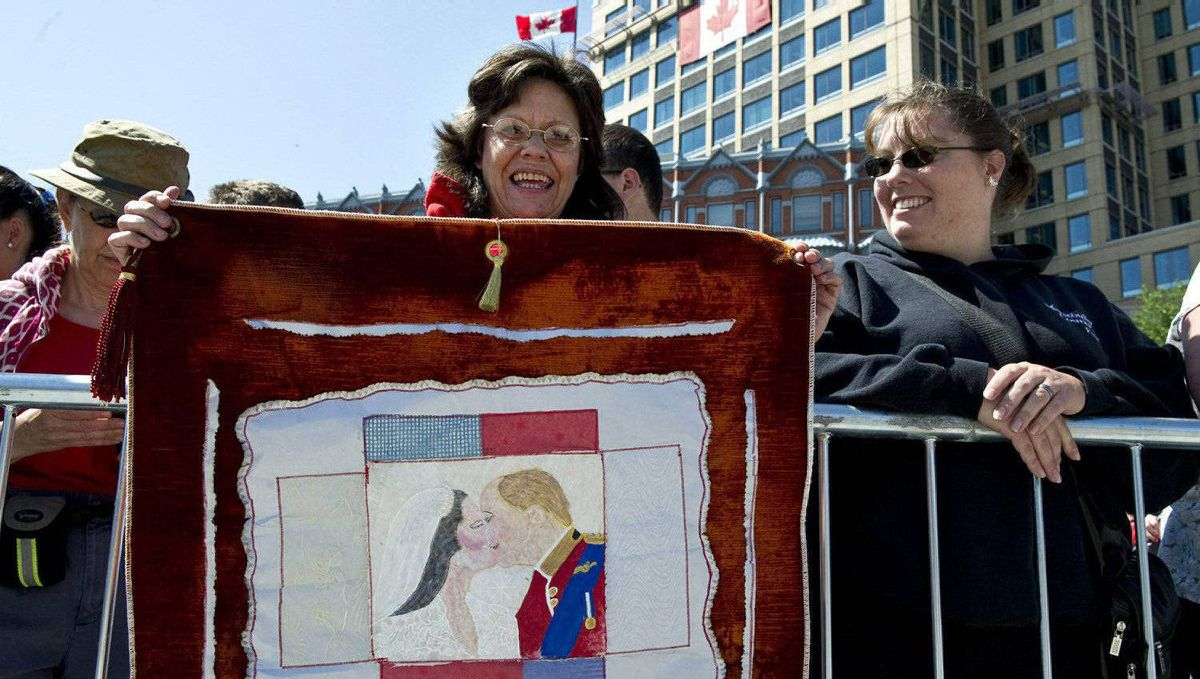 Francine Dorion holds up a handmade tapestry as she waits for the arrivel of the Duke and Duchess of Cambridge at the War Memorial, Thursday, June 30, 2011 in Ottawa.