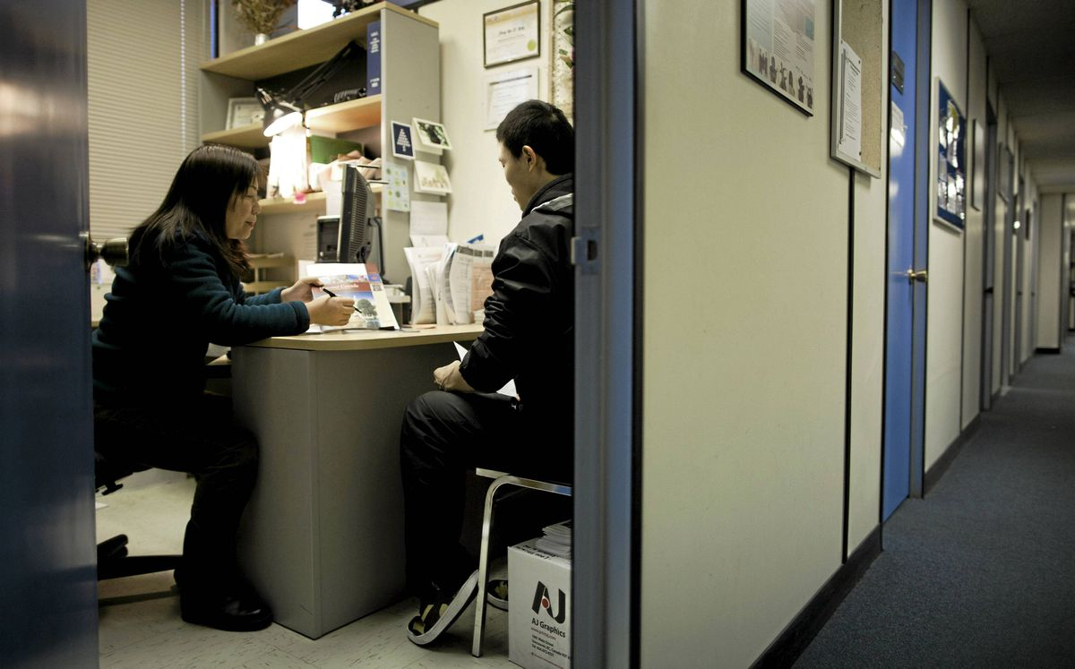Chinese immigrants speak to Flora Lung, left, a Settlement Services counsellor, about applying for a Social Insurance Number at the MOSAIC non-profit organization in Vancouver.