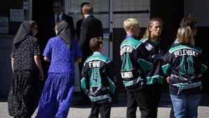Hutteritte women, left, walk past minor hockey league players to attend the funeral service for Rick Rypien. THE CANADIAN PRESS/Jeff McIntosh