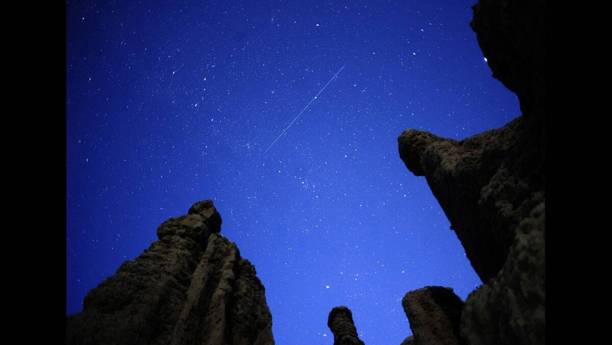 A meteor streaks though the night sky over the village of Kuklici, known for its hundreds of naturally formed stones which resemble human beings, near Kratovo, August 13, 2011.