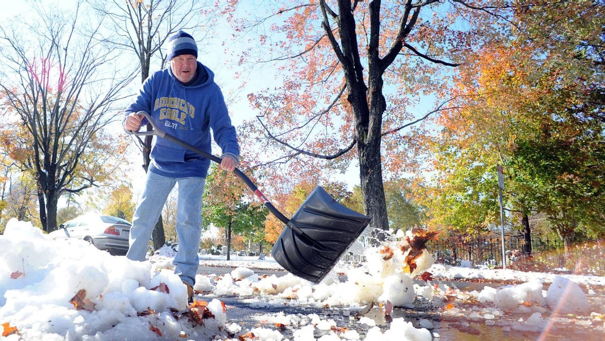 Jim Nisula of Doylestown, Pennsylvania shovels snow and ice outside his home after a winter storm October 30, 2011 in Doylestown, Pennsylvania.