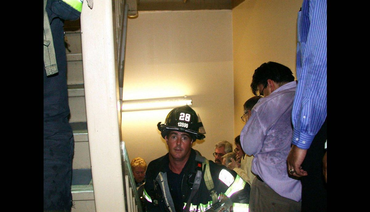 Engine 28 firefighter Mike Kehoe, from Staten Island, assists in the evacuation effort in a stairwell of Tower One on Sept. 11, 2001 during the attacks on the World Trade Center towers in New York.