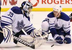 Toronto Maple Leafs goalie Vesa Toskala, left, of Finland, makes a save as teammate Ian White looks to clear the rebound during third period NHL action against the Washington Capitals in Toronto Saturday, November 21, 2009. The Toronto Maple Leafs defeated the Washington Capitals 2-1 in a shootout. THE CANADIAN PRESS/Darren Calabrese